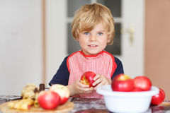 Adorable little child helping and baking apple pie in home''s ki Royalty Free Stock Photography