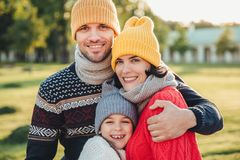 Adorable little child stand close to her affectionate parents, enjoy spending time together, embrace each other, smile happily, lo royalty free stock image