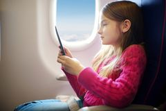 Adorable little child traveling by an airplane. Girl sitting by aircraft window and reading her ebook during the flight. Traveling Stock Photography