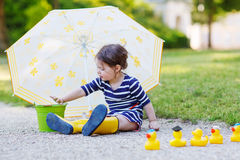 Adorable little child in yellow rain boots and umbrella in summe Stock Photos