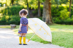 Adorable little child in yellow rain boots and umbrella in summe Stock Images