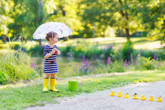 Adorable little child in yellow rain boots and umbrella in summe. R park Royalty Free Stock Photos
