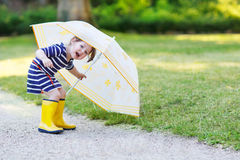 Adorable little child in yellow rain boots and umbrella in summe Royalty Free Stock Image