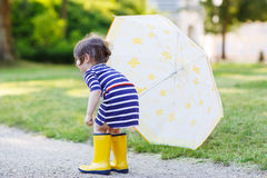 Adorable little child in yellow rain boots and umbrella in summe Stock Image