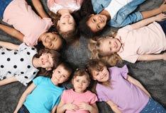 Adorable little children lying on floor together indoors. Kindergarten playtime activities royalty free stock images