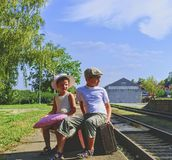 Adorable little children on a railway station, waiting for the train with vintage suitcases. Traveling, holiday and chilhood conce. Pt. Travel insurance concept royalty free stock photos