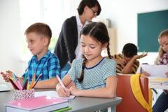 Adorable little children sitting at desks. In classroom. Elementary school stock photo