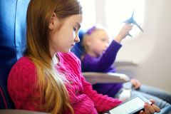 Adorable little children traveling by an airplane. Girl sitting by aircraft window and reading her ebook during the flight. Travel Stock Image