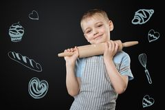 Pretty child standing with a rolling pin and looking cute royalty free stock photos