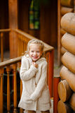 Adorable little curly blond girl in beige knitted sweater smiles Royalty Free Stock Photo