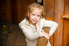 Adorable little curly blond girl in beige knitted sweater smiles Royalty Free Stock Images