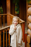 Adorable little curly blond girl in beige knitted sweater smiles Stock Photos