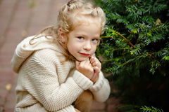 Adorable little curly blond girl in beige knitted sweater smiles Stock Photo