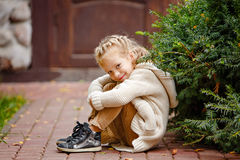 Adorable little curly blond girl in beige knitted sweater smiles Royalty Free Stock Photos