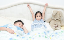 Adorable little cute girl awaked up in her bed and brother sleep Stock Photos