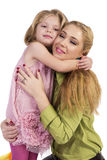 Adorable little daughter hugging her happy mother Stock Photo