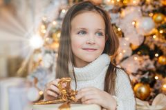 Adorable little female child with warm blue eyes, long dark hair, wears knitted warm white sweater, holds present stands against d stock photo