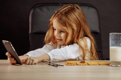 Adorable little girl playing with smartphone in Daddy s office. Adorable little female kid looking cartoons on smartphone in Daddy s office while having a snack royalty free stock photos