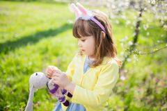 Adorable little funny bunny girl holding rabbit toy in the spring blossom garden. Easter time royalty free stock images