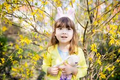 Adorable little funny bunny girl holding rabbit toy in the spring blossom garden. Easter time stock images