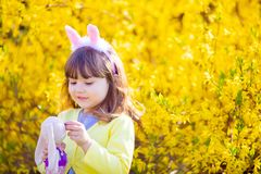 Adorable little funny bunny girl holding rabbit toy in the spring blossom garden royalty free stock photos