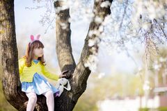 Adorable little funny bunny girl sitting at the blooming three at sunny spring day stock photo