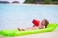 Adorable little girl on air inflatable mattress in Stock Photos