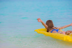 Adorable little girl on air inflatable mattress in the sea Royalty Free Stock Photo