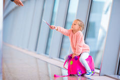 Adorable little girl in airport have fun waiting for boarding. Adorable little girl at airport sitting on suitcase Stock Photography