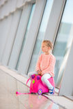 Adorable little girl in airport with her luggage Stock Photography