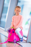 Adorable little girl in airport with her luggage waiting for boarding Stock Images