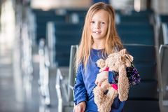 Adorable little girl in airport indoor before boarding. Adorable little girl in airport with her luggage Royalty Free Stock Images