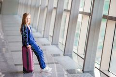 Adorable little girl in airport near big window. Adorable little girl in airport with her luggage Royalty Free Stock Photography