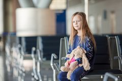 Adorable little girl in airport near big window indoor. Adorable little girl with her favourite toy in airport indoor Royalty Free Stock Photography