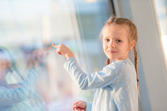 Adorable little girl in airport near big window looking at big aircraft Stock Images