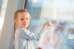 Adorable little girl in airport near big window waiting for boarding Stock Photo