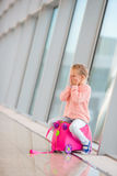 Adorable little girl in airport sitting on luggage Stock Photos