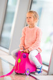 Adorable little girl in airport sitting on luggage Royalty Free Stock Photo