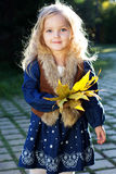 Adorable little girl with autumn leaves in park Stock Photo
