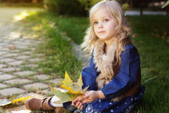 Adorable little girl with autumn leaves in park Stock Photography