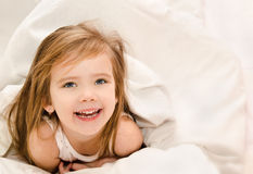 Adorable little girl awaked up in her bed Royalty Free Stock Photos