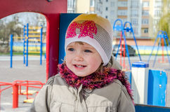 Adorable little girl baby with beautiful eyes, playing on a wooden swing at the amusement park, dressed in a raincoat with a hood, Royalty Free Stock Photography
