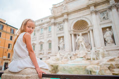Adorable little girl background Trevi Fountain, Rome, Italy. Happy toodler kid enjoy italian vacation holiday in Europe. Stock Photo