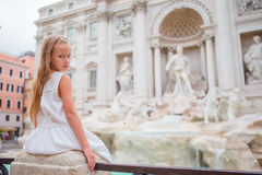Adorable little girl background Trevi Fountain, Rome, Italy. Happy toodler kid enjoy italian vacation holiday in Europe. Young beautiful girl near fountain Stock Image