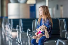 Adorable little girl with baggage in airport waiting for boarding. Adorable little girl having fun in airport sitting on suitcase waiting for boarding Stock Photos