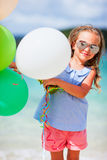Adorable little girl with balloons at beach Royalty Free Stock Image
