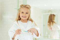 adorable little girl in bathrobe holding toothbrush with toothpaste and smiling royalty free stock photography