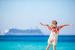 Adorable little girl at beach background big cruise lainer in Greece Royalty Free Stock Photo