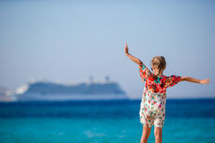 Adorable little girl at beach background big lainer in Greece Stock Photo
