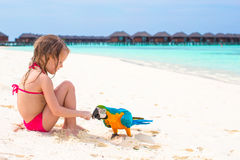 Adorable little girl at beach with big colorful. Bird Royalty Free Stock Photography